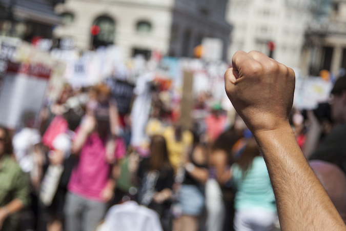 A raised fist of a protestor at a political demonstration By ink drop AdobeStock_213679862