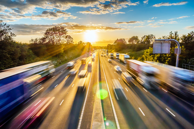 Heavy traffic moving at speed on UK motorway in England at sunset By Jevanto Productions AdobeStock_298379174
